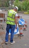 Sicherheitsbeamte nahe Straßenarbeiten Stockbild
