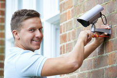 Sicherheitsberater Fitting Security Camera zur Hausmauer Lizenzfreies Stockfoto