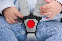 Sicherheitsgurt mit dem roten Knopf, der ein Baby in seinem Autositz schützt Stockbild