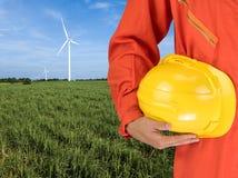 Sicherheitsklage und -hand halten gelben Sturzhelm mit Windkraftanlagen gener Stockfoto
