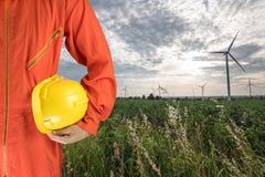 Sicherheitsklage und -hand halten gelben Sturzhelm mit Windkraftanlagen gener Lizenzfreie Stockbilder