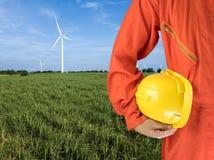 Sicherheitsklage und -hand halten gelben Sturzhelm mit Windkraftanlagen gener Stockfotografie