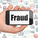 Sicherheitskonzept: Hand, die Smartphone mit Betrug auf Anzeige hält Stockbild