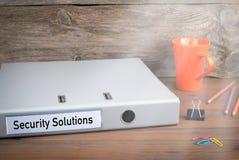 Sicherheitslösungen Ordner, Kaffeetasse und farbige Bleistifte auf hölzernem Schreibtisch Stockbilder