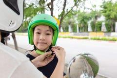 Sicherheitsreitkonzept Bemuttern Sie das Versuchen, einen Fahrradsturzhelm zu seinem zu tragen stockfotografie