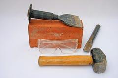 Sicherheitsschutzbrillen, -hilfsmittel und -ziegelstein. Lizenzfreie Stockfotografie