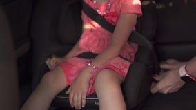 SicherheitsSicherheitsgurt befestigen Kinderautositz mit der Mutter und daughterYoung kaukasischer wei?er Mutter, die helles klar stock video footage