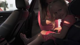 SicherheitsSicherheitsgurt befestigen Kinderautositz mit Mutter und Tochter Junge kaukasische wei?e Mutter, die helles klares des stock footage