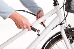 Sichern des Fahrrades mit einer Kette mit einem Schlüssel Lizenzfreie Stockfotografie