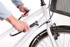 Sichern des Fahrrades mit einer Kette mit einem Schlüssel Stockbild