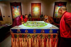 Sichuan monks creating sacred Buddhist art, Shenzhen. A group of monks from Sichuan province carefully apply special colored inks to create sacred Buddhist stock image