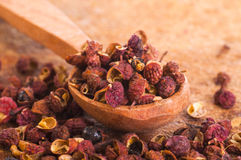 Sichuan pepper in spoon. Sichuan pepper or Chinese Pepper in wooden spoon on wooden background Stock Photo