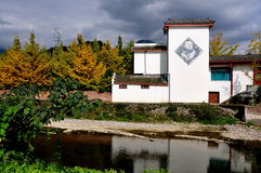 Sichuan Province, China: Chinese House & Yellow Gingko Trees. A white Chinese house with a diamond-shaped wall mural overlooks a small river next to a grove Royalty Free Stock Images