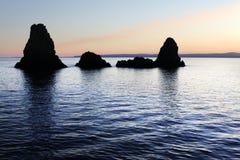 Sicilië: Cyclopische Eilanden in Acitrezza bij zonsondergang. Stock Foto