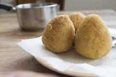 Sicilian arancine fried in boiling oil. Street food : fried sicilian rice balls or arancini Stock Photography