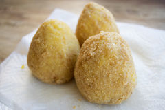 Sicilian arancine fried in boiling oil. Street food : fried sicilian rice balls or arancini Royalty Free Stock Images