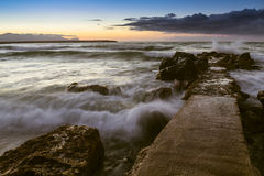 The Sicilian coast at sunset. Sunset on a small pier by the beach at Balestrate city in western Sicily (Italy Stock Image