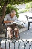 Sicilian man reading newspaper. Elderly man sitting on a chair in a public park reading a newspaper in the city of scicli in Sicily royalty free stock photography