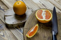 Sicilian oranges and knife with black knob rests on a wooden board, which stands on a wood table royalty free stock photos