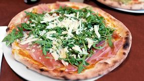 Sicilian pizza topped with ham, arugula and pecorino cheese Royalty Free Stock Image
