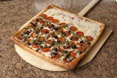 Sicilian Pizza. On wood pizza peel. Fresh out of the oven royalty free stock images