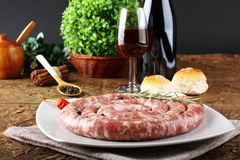 Sicilian raw sausage with pepper and rosemary. On complex background Stock Images