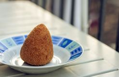 Sicilian snack, fried ball of rice arancino on a plate, tipical street food of Sicily royalty free stock photography