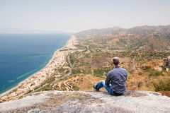 Sicily Coastline. Young Man Sitting on a High Hill and Enjoying the View in Sicily Stock Photography