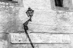 Sicily Lantern. Lantern in Sicily, Italy with illegible fading sign on midday. Vintage Black and White. Strong Shadows Stock Photos