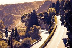 Sicily sunset with curvy serpentine road in green mountains - beautiful panorama of Taormina.  stock photography