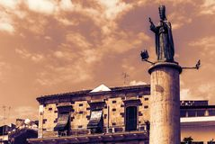 Sicily sunset, historical street of Acitrezza, Catania, facade of old buildings with monument of San Mauro.  royalty free stock images