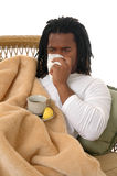 Sick. A young man with a cold covered in a blanket and drinking hot tea Royalty Free Stock Photos