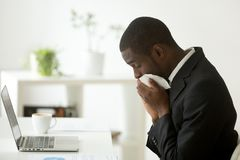 Sick african american businessman sneezing in tissue working in. Sick young african-american businessman wearing suit caught cold sneezing in tissue working in Royalty Free Stock Photography