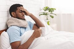 Sick african-american man drinking hot healing tea in bed. Feeling bad. Sick african-american man drinking hot healing tea in bed, touching his forehead, empty stock images