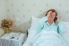 Sick aged woman calling her doctor. Royalty Free Stock Photo