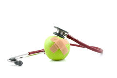Sick apple with patches and stethoscope Royalty Free Stock Photography