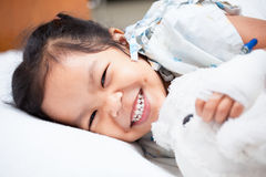 Sick asian child girl is lay down on the bed and smiling Royalty Free Stock Photo
