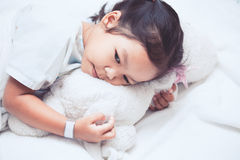 Sick asian child girl is lying in the bed and hugging her doll. In the hospital stock photos