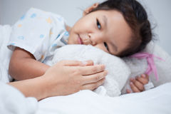 Sick asian child girl is lying in bed and mother hold her hand Royalty Free Stock Images
