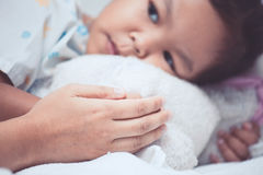 Sick asian child girl is lying in bed and mother hold her hand. Sick asian child girl is lying in the bed and mother holding her hand with love in the hospital royalty free stock photos