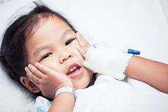 Sick asian child girl is lying in the bed and touch her face. In the hospital stock photography