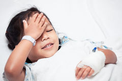 Sick asian child girl is lying in the bed and touch her forehead. In the hospital royalty free stock photography