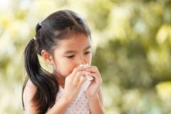 Sick asian child girl wiping and cleaning nose with tissue Stock Image
