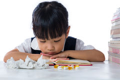 Sick Asian Chinese little girl wearing uniform studying Royalty Free Stock Image