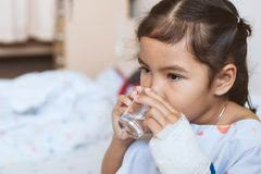 Sick asian little child girl hand is drinking fresh water stock image