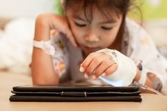 Sick asian little child girl who have IV solution bandaged playing digital tablet to relax. While staying in the hospital royalty free stock photo