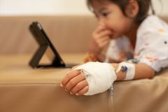 Sick asian little child girl who have IV solution bandaged playing digital tablet to relax. While staying in the hospital royalty free stock photography
