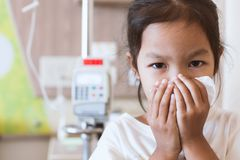 Sick asian child girl wiping and cleaning nose with tissue. Sick asian little child girl wiping and cleaning nose with tissue on her hand in the hospital Royalty Free Stock Images