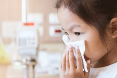 Sick asian child girl wiping and cleaning nose with tissue. Sick asian little child girl wiping and cleaning nose with tissue on her hand in the hospital Stock Photos