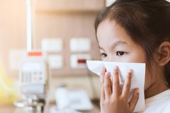Sick asian child girl wiping and cleaning nose with tissue. Sick asian little child girl wiping and cleaning nose with tissue on her hand in the hospital Royalty Free Stock Image